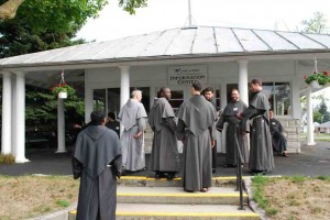 Friars gather in front of the Shrine information booth