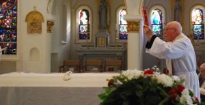 Fr. Phil Schneider places the Book of Gospels on the casket.