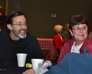 Br. Paul Clark shares a laugh with Donna Staser.