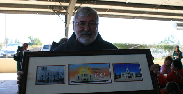 Fr. Don Adamski holds the beautiful gift presented by the Centennial Committe.