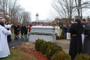 Friars, family, and friends extend their hands over the casket to offer a blessing.