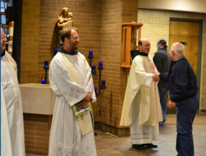 Friars Florian Tiell, John Bamman, and Jim Kent greet people after mass (at St. Anthony of Padua in Clarksville, IN)