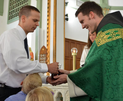 Fr. Bryan receives the offertory gifts from his brother Blake and his nieces and nephews.