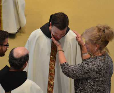 Nancy Hajovsky, Fr. Bryan's mother, shares the joy of his ordination after assisting with his investiture.
