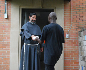 Br. Don Bassana, OFM Conv., gives a sandwich to someone who is hungry in San Antonio, Texas.