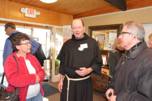 Fr. Jim Kent talks with two friends before the spaghetti dinner at Franciscan Retreats and Spirituality Center.