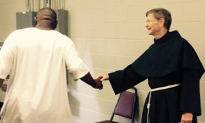 Fr. Christian Moore visits with guests at the Franciscan Kitchen in Louisville, KY.