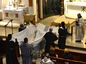 The pall is placed on the casket.